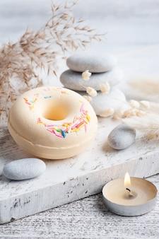 목욕 폭탄 도넛과 흑백 스타일의 소박한 배경에 마른 꽃 스파 구성. 양초와 소금. 미용 치료 및 휴식