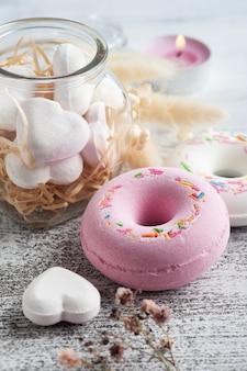 Спа-композиция с пончиками-бомбой для ванны и сухими цветами на деревенском фоне в монохромном стиле. свечи и соль. косметические процедуры и отдых
