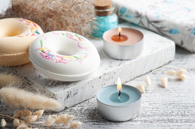 목욕 폭탄 도넛과 흑백 스타일의 시골 풍 테이블에 마른 꽃 스파 구성. 양초와 소금. 미용 치료 및 휴식