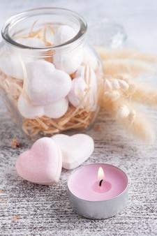 Спа-композиция с сердечками бомбы для ванны и сухими цветами на деревенском фоне в монохромном стиле. свечи и соль. косметические процедуры и отдых