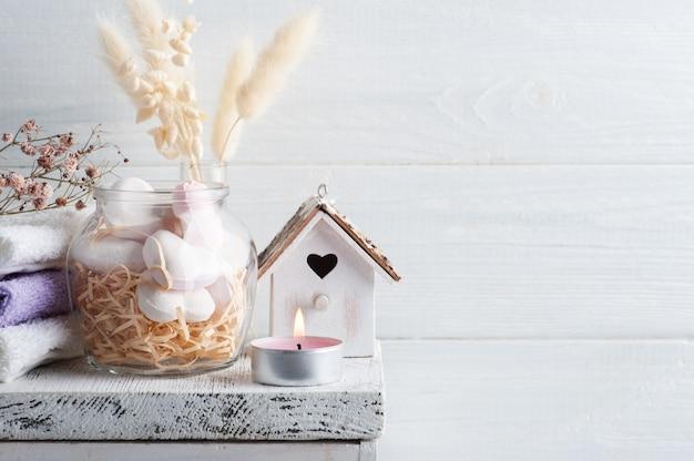 Спа-композиция с сердечками бомбы для ванны и сухими цветами на деревенском фоне в монохромном стиле.