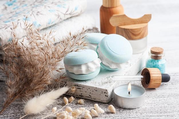 Спа-композиция с миндальным печеньем для ванны и сухими цветами на деревенском столе в монохромном стиле. свечи и соль. косметические процедуры и отдых