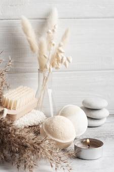 Спа-композиция с бомбочками для ванн и сухими цветами на деревенском столе в монохромном стиле. полотенце со свечами и белой галькой. терапия массажем горячими камнями. косметические процедуры и отдых