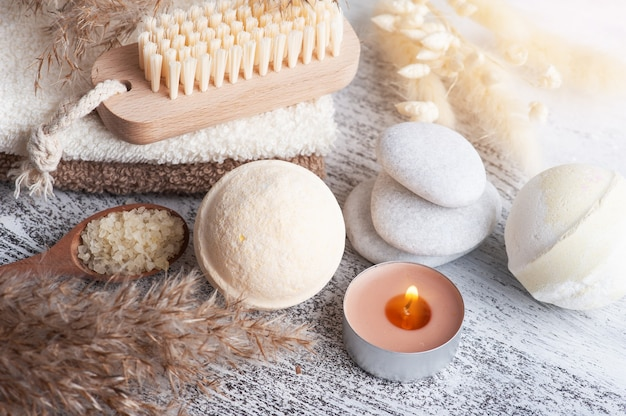 Spa composition with bath bombs and dry flowers on rustic table in monochrome style. towel with candles and white pebbles. hot stone massage therapy for one person. beauty treatment and relax