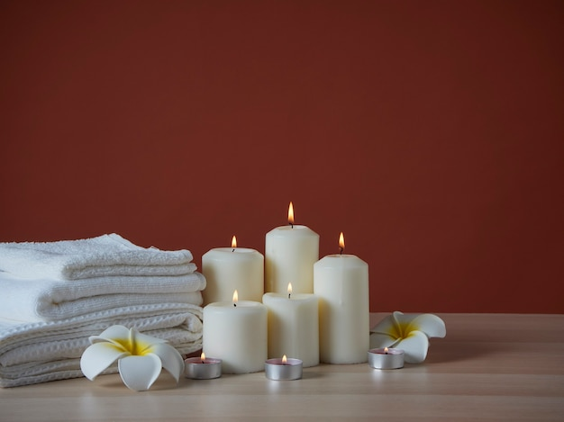 Spa composition with burning aromatic candles and plumeria flowers on wooden table