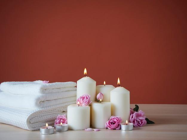 木製のテーブルに香りのキャンドルとバラを燃やすスパ構成