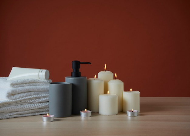 Spa composition with burning scented candles on wooden table