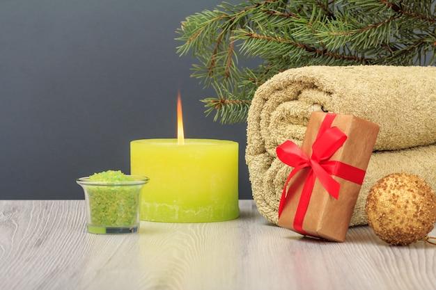 선물 상자와 장난감 공이 있는 스파 구성입니다. 부드러운 테리 수건, 바다 소금이 든 그릇, 불타는 촛불, 회색 배경에 전나무 가지