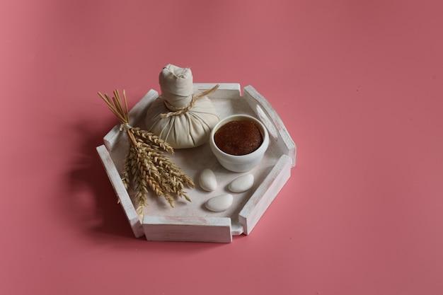 Composizione spa con borsa a base di erbe e scrub naturale su sfondo rosa