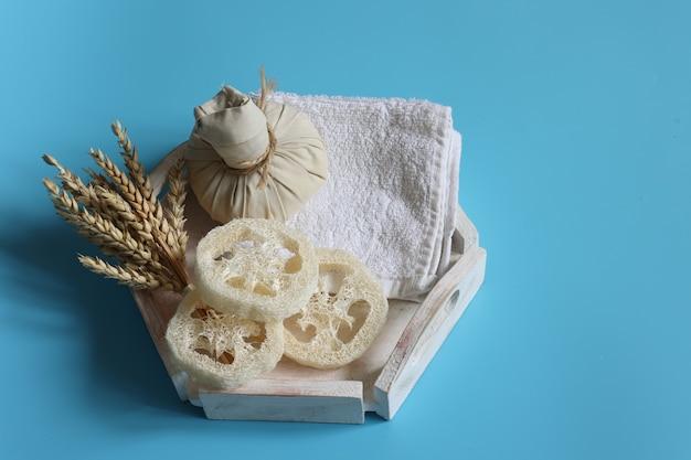 Composizione spa con borsa per massaggi alle erbe, luffa, asciugamano e grano su sfondo blu, spazio copia.