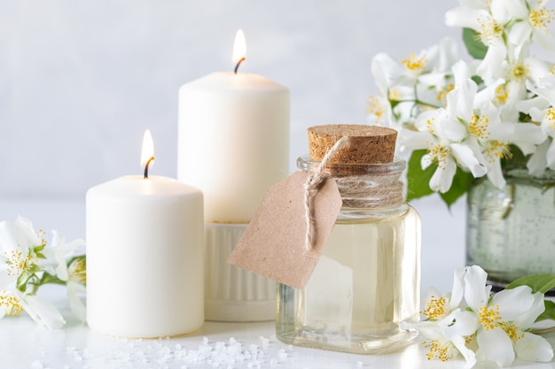 Spa composition with jasmine flowers on a white table close up.