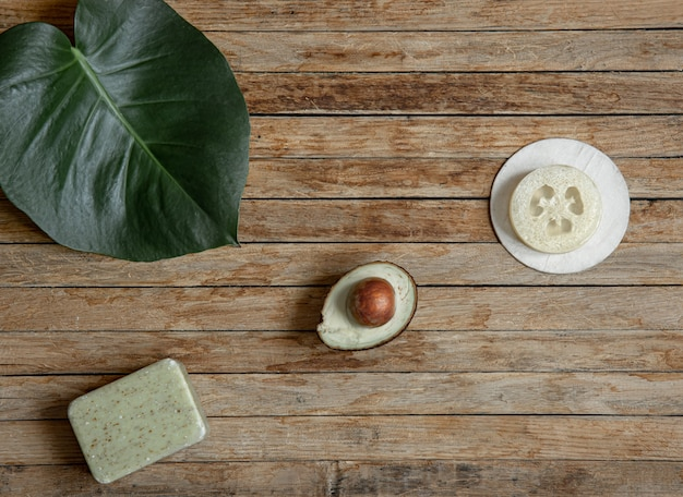 Spa composition with natural soap, avocado and loofah on a wooden surface top view.