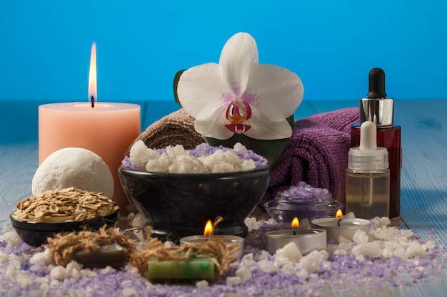 Spa composition with orchid flower, bowl with sea salt, bottles with aromatic oil, soap, scrub, candles and towels on wooden board and blue background