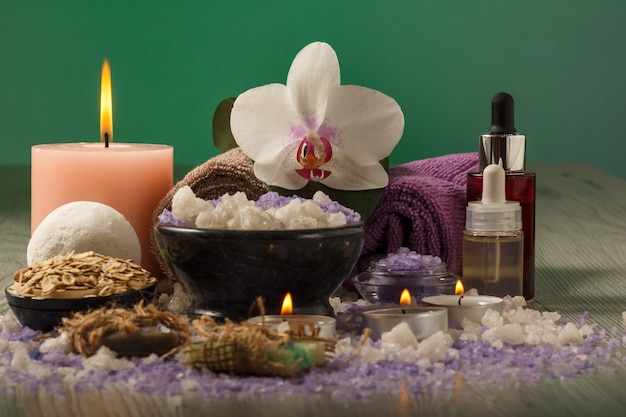 Spa composition with orchid flower, bowl with sea salt, bottles with aromatic oil, soap, scrub, candles and towels on wooden board and green background