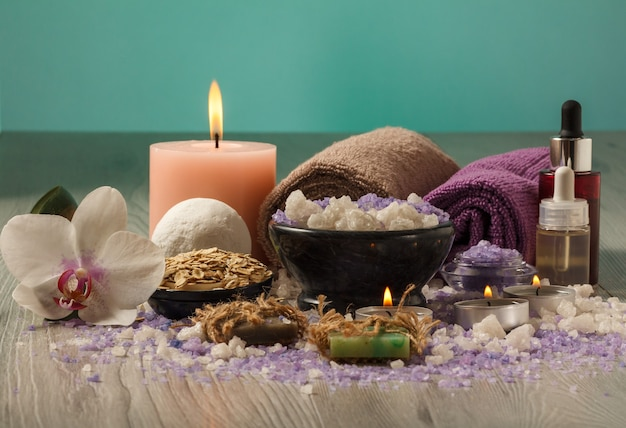Spa composition with orchid flower, bowl with sea salt, bottles with aromatic oil, soap, scrub, candles and towels on wooden board and light green background
