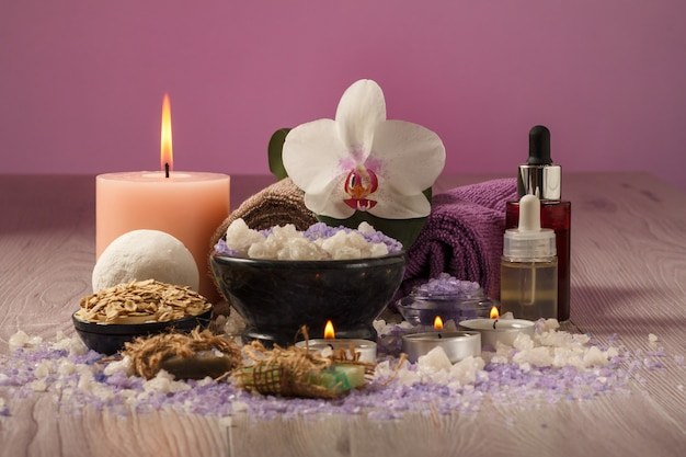 Spa composition with orchid flower, bowl with sea salt, bottles with aromatic oil, soap, scrub, candles and towels on wooden board and pink background