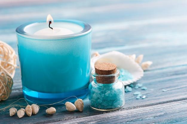 青い木製の背景に香りのキャンドルと海塩のスパ構成。美容トリートメントとコピースペースでリラックス
