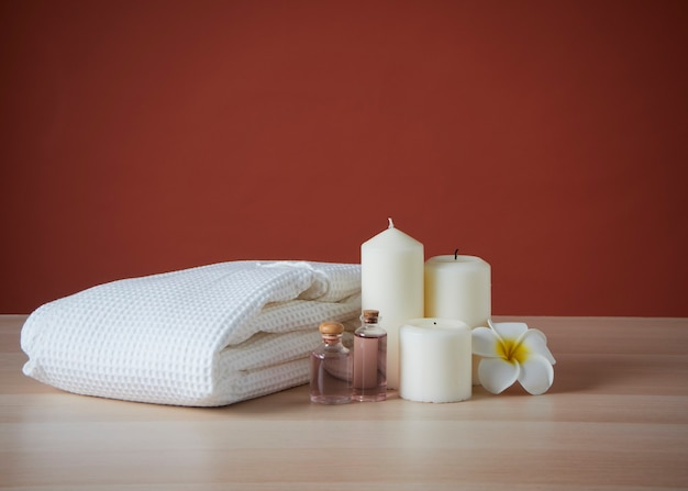 Spa composition with scented candles and plumeria flower on wooden table