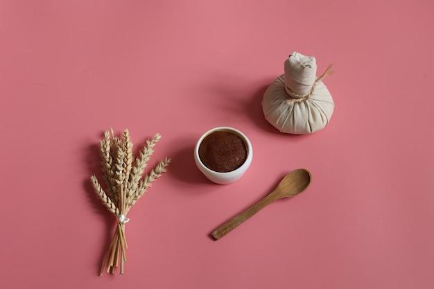 Composizione spa con borsa a base di erbe scrub e cucchiaio di legno su sfondo rosa