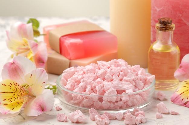 海の塩、アロマオイル、グレーと白のコンクリートの上に花をつけた手作り石鹸を使ったスパの組成