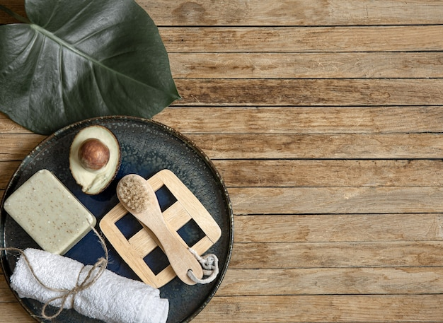 Spa composition with soap, avocado towel, brush and leaf on wooden surface copy space.