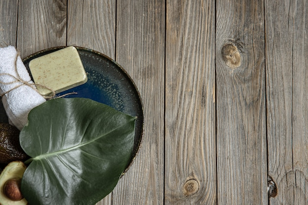 Composizione spa con sapone, avocado, asciugamano e foglia sulla superficie in legno copia spazio.