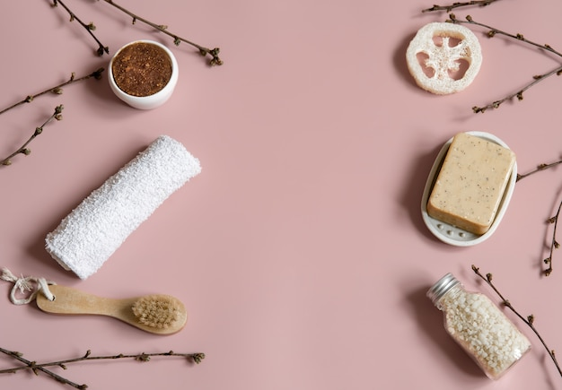 Spa composition with soap, brush, loofah, sea salt and towel among spring tree branches top view.