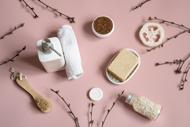 Spa composition with soap, brush, loofah, sea salt and towel among spring tree branches.
