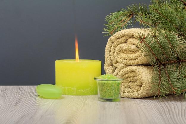 부드러운 테리 수건, 아로마 오일 한 병, 바다 소금이 든 그릇, 비누, 회색 배경에 불타는 촛불이 있는 스파 구성.