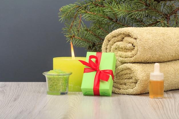 부드러운 테리 수건, 아로마 오일이 든 병, 선물 상자, 바다 소금이 든 그릇, 촛불, 회색 배경에 전나무 가지가 있는 스파 구성