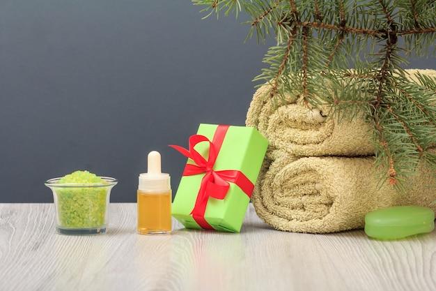 부드러운 테리 수건, 아로마 오일이 든 병, 선물 상자, 바다 소금이 든 그릇, 비누, 회색 배경에 전나무 가지가 있는 스파 구성