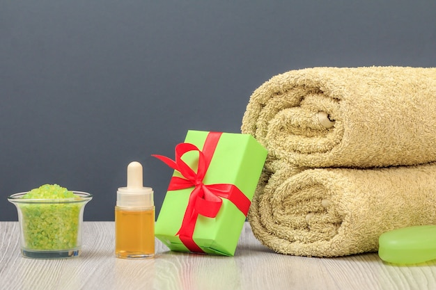 부드러운 테리 수건, 선물 상자, 아로마 오일 한 병, 바다 소금과 비누가 회색 배경에 있는 스파 구성.