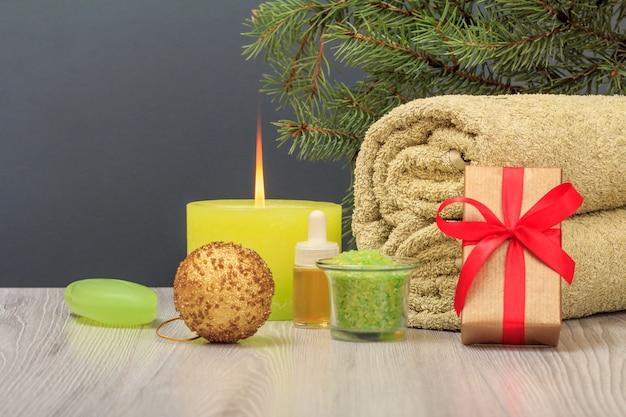 부드러운 테리 수건, 선물 상자, 아로마 오일 한 병, 바다 소금이 든 그릇, 반짝이는 공, 비누가 회색 배경에 있는 스파 구성.