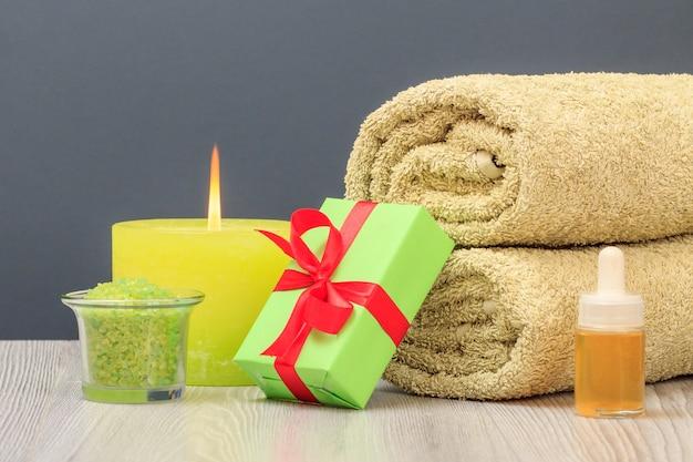 부드러운 테리 수건, 선물 상자, 바다 소금이 든 그릇, 아로마 오일 한 병, 회색 배경에 불타는 촛불이 있는 스파 구성.
