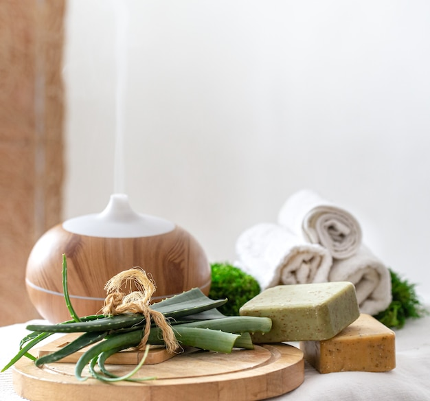 ボディケア製品を備えたモダンなオイルディフューザーの香りを持つスパ組成物。ツイストした白いタオルとアロエベラ。体と健康のためのウェルネスの概念。