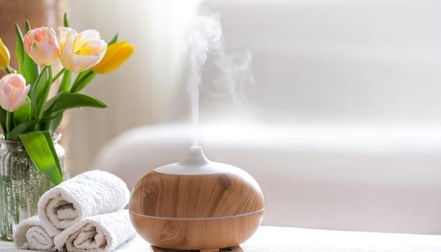 ボディケア製品を備えたモダンなオイルディフューザーの香りを持つスパ組成物。ツイスト白いタオル、春の緑と花。体と健康管理のためのスパのコンセプト。