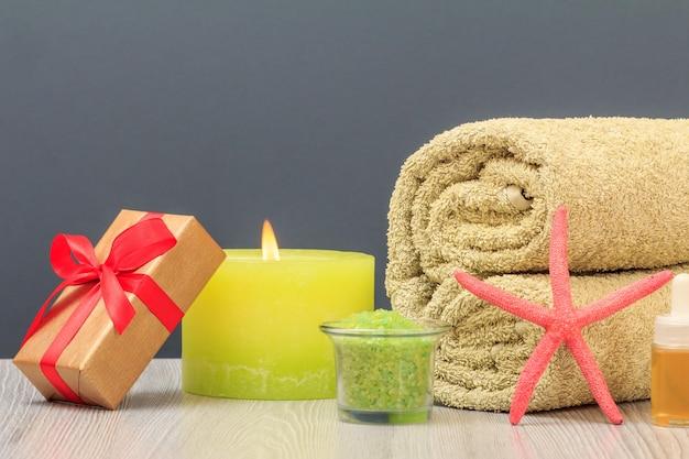 수건, 선물 상자, 바다 소금, 촛불이 있는 스파 구성.