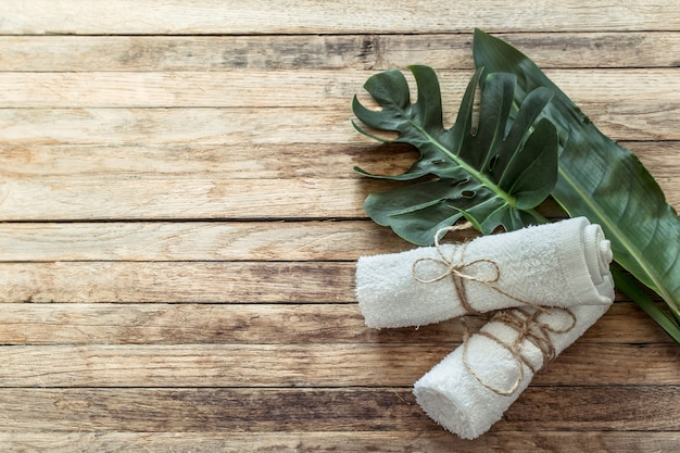 Spa composition with towels and tropical leaf on a wooden wall.