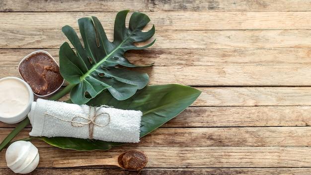Composizione spa con asciugamani e foglia tropicale su una parete in legno.