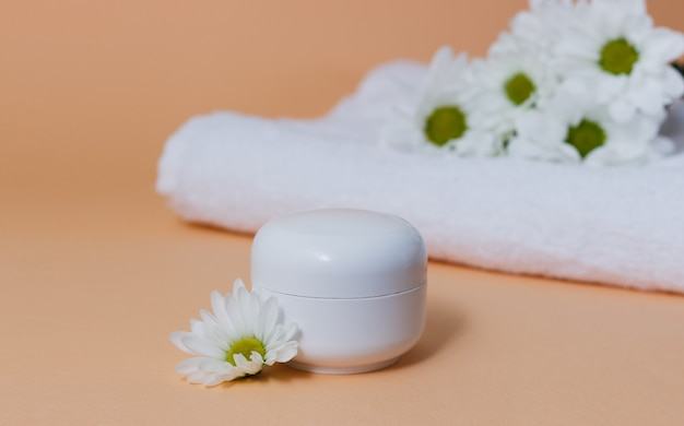 Spa composition with white towel and bottle of cream on beige surface