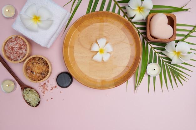 スパのコンセプト。スパセットで美容とファッションのコンセプト。香りの花の水。リラクゼーションと禅、ボウル、バスソルトと花、タオル、天然石鹸を備えたスパセッティングフラットレイ。上面図。
