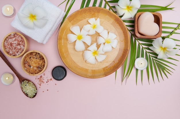 Spa concept. beauty and fashion concept with spa set. perfumed flowers water. relaxation and zen, spa setting flat lay with bowl, bath salt and flowers, towel and natural soap. top view.