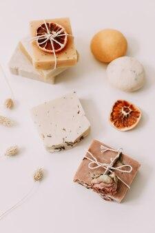Спа-концепция средств по уходу за телом и кусков натурального домашнего мыла на белой поверхности
