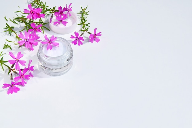 Крем-концепция спа в стеклянной банке с розовыми цветами и зелеными листьями на белом фоне. копировать пространство.