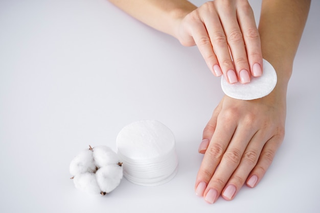 Spa concept. hands of a young woman with a cotton disk, white cotton flower on a white background. female manicure. cotton flower.
