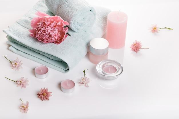 Концепция спа в день святого валентина, день рождения, розовый пион, свечи, синие полотенца, цветы. весной или летом фон