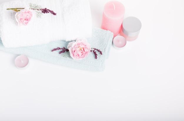 バレンタインデー、誕生日、ピンクのバラ、キャンドル、青いタオル、花のスパのコンセプト。春または夏の背景