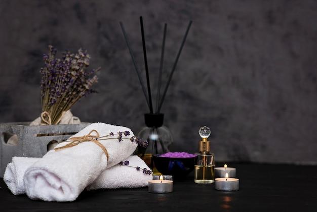스파 개념. 편안한 목욕, 아로마 오일, 양초, 하얀 수건, 마른 라벤더 꽃, 회색 배경에 향수 라벤더 소금. 아로마 테라피