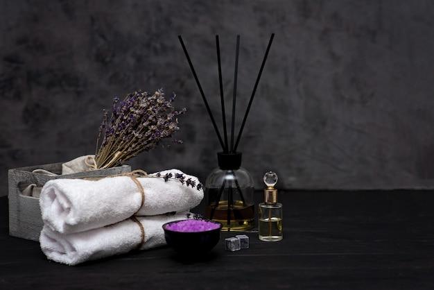 스파 개념. 편안한 목욕, 아로마 오일, 하얀 수건, 마른 라벤더 꽃, 회색 배경에 향수 라벤더 소금. 아로마 테라피