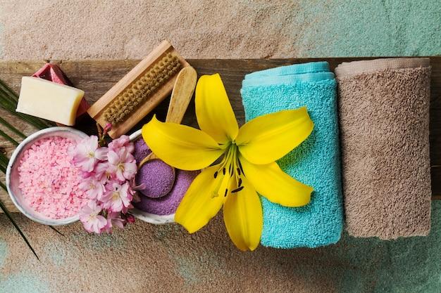 スパコンセプト。テキストのための場所で美しいスパ製品のトップビュー。美しい花、タオル、スパソルト、手作り石鹸のエッセンシャルオイル。